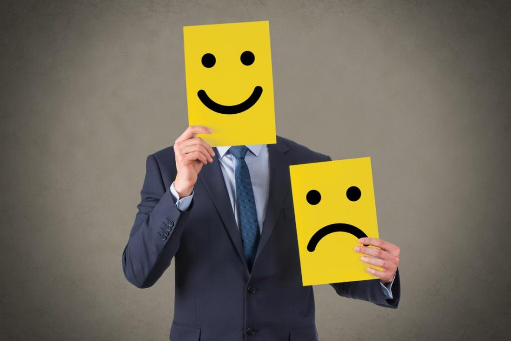 This image has an empty alt attribute; its file name is a-man-holding-cards-with-happy-and-sad-faces-1024x683.jpg